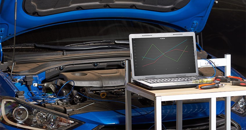 Laptop on trolley in front of car with bonnet open, running diagnostics